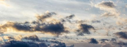 Panorama of gorgeous cloudscape at sunset. Beautiful nature background with golden fluffy clouds Royalty Free Stock Photo