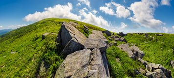 Panorama of gorgeous mountainous summer landscape. Huge rocky formations on the steep grassy slopes. beautiful cloud formation on the blue sky. Ukrainian Stock Photography