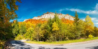 Panorama of gorgeous serpentine in autumn forest. Huge rocky formation on the hill above the path. beautiful nature and weather. colorful foliage royalty free stock photos