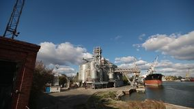 Panorama of grain terminal at seaport on sunny day. Cereals bulk transshipment to vessel loading grain crops on bulk. Panorama of grain terminal at seaport on stock video footage