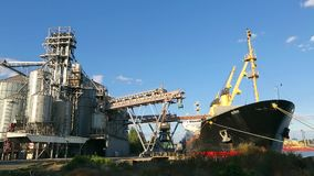 Panorama of grain terminal at seaport on sunny day. Cereals bulk transshipment to vessel loading grain crops on bulk. Panorama of grain terminal at seaport on stock footage