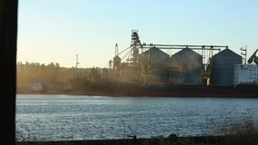 Panorama of grain terminal at seaport on sunny day. Cereals bulk transshipment to vessel loading grain crops on bulk. Timelapse of grain terminal at seaport on stock footage