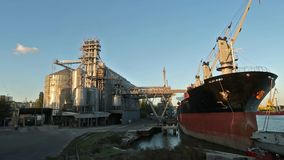 Panorama of grain terminal at seaport on sunny evening. Cereals bulk transshipment to vessel loading grain crops on bulk. Panorama of grain terminal at seaport stock footage