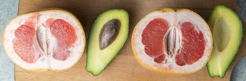 Panorama of grapefruit and avocado on the kitchen board stock photo