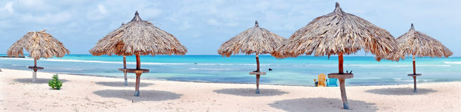 Panorama from grass umbrellas at the beach on Aruba island Stock Photos