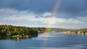 Panorama of green coast with villages and rainbow Royalty Free Stock Photography