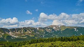 Panorama of the green hills and snow in Carpathian mountains with the blue sky and white clouds. In the summer Stock Images