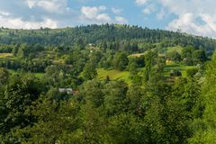 A panorama of green hills and somewhere the roofs of houses looking out among the greenery. For your design Stock Images