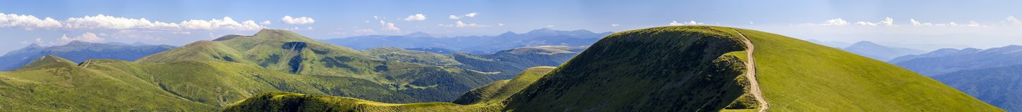 Panorama of green hills in summer mountains with gravel road for. Travelling by car Royalty Free Stock Photos