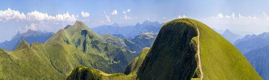 Panorama of green hills in summer mountains with gravel road for travelling by car.  stock photography