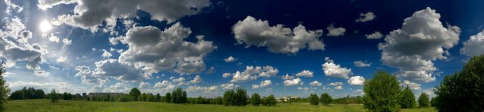 Panorama of a green meadow with bright green vegetation. Against the background of a bright blue sky with fluffy white clouds.  Stock Image