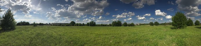 Panorama of a green meadow with bright green vegetation. Against the background of a bright blue sky with fluffy white clouds.  Royalty Free Stock Photography