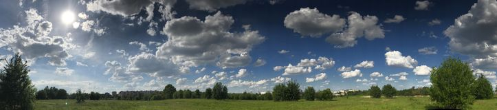 Panorama of a green meadow with bright green vegetation. Against the background of a bright blue sky with fluffy white clouds.  Royalty Free Stock Image