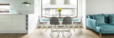 Panorama of grey chairs at table with yellow flowers next to blu. E settee in living room interior. Real photo Stock Image