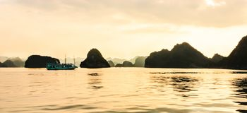 Panorama of Ha Long bay islands, tourist boat and seascape in the evening with golden light reflection on water, Ha Long, Vietnam.  royalty free stock photos