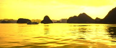 Panorama of Ha Long bay islands, tourist boat and seascape in the evening with golden light reflection on water, Ha Long, Vietnam.  stock images