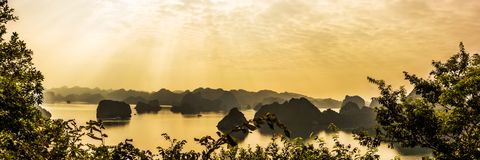 Panorama of Ha Long bay islands, tourist boat and seascape in the evening with golden sunlight beam reflection on water, Ha Long. Vietnam stock images