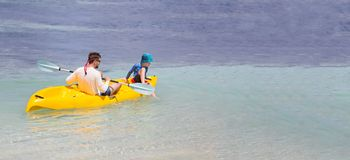 Family on vacation. Panorama of happy family of two, father and son, in rashguards enjoying kayaking together, healthy family activity during summer tropical Stock Photo