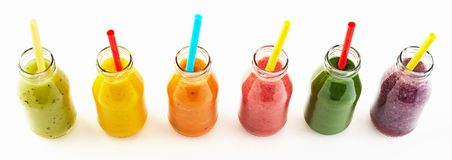 Panorama of healthy veggie and fruit smoothies. Panorama of healthy fresh vegetable and fruit smoothies in clear glass bottles with straws viewed top down stock photos