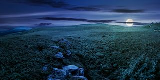 Panorama of the hillside meadow at night. In full moon light. lovely summer landscape with boulders among the grass. location Runa mountain, Ukraine Stock Images