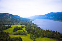 Panorama hilly banks river covered lush green trees leaving blue Royalty Free Stock Photo