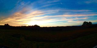 Panorama- himmel för landssolnedgång Arkivfoto