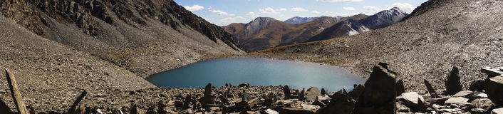 Panorama about holy lake in Tibet. Panoramic view of a sacred lake of the Tibetan Kham. Shorten, cairn and pile of stones left by pilgrims at 5000 m altitude Stock Photography