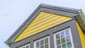 Panorama Home with yellow wall and glass windows against cloudy sky in Daybreak Utah. The roof is covered with a sheet of fresh snow during winter season stock image