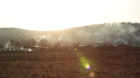 Panorama horizontal, grama ardente perto da floresta com lotes do fumo ao lado das casas de madeira no por do sol contra a montan filme