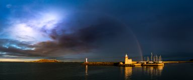 Panorama of Howth Harbour in County Dublin under a dramatic stormy cloudy sky with a rainbow stock images