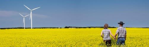 Panorama image of caucasian couple walking in yellow canola field. Stock Photo