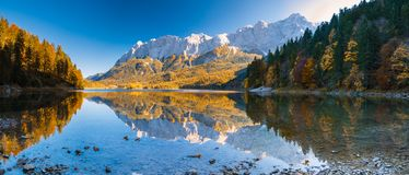 Panorama Image of Eibsee during autumn with the Zudspitze in the background and water reflections royalty free stock photos