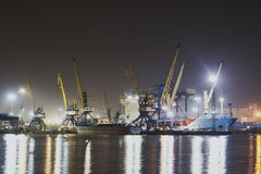 Panorama image of the illuminated cargo port in Novorossiysk, Russia at night with container terminals, cargo ship and cranes and Stock Photos