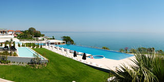 Panorama of infinity swimming pool by beach Stock Images