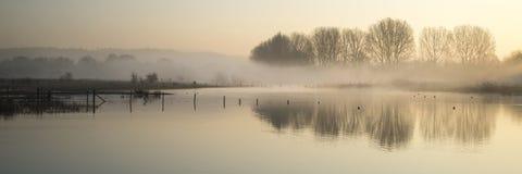 Panorama krajobraz jezioro w mgle z słońce łuną przy wschodem słońca fotografia stock