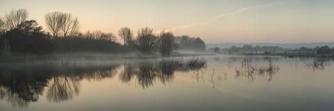 Panorama krajobraz jezioro w mgle z słońce łuną przy wschodem słońca Obraz Stock