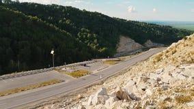 Panorama kronkelige weg door het hout in de bergen Weergeven van de bergweg van hierboven Mening van stock videobeelden