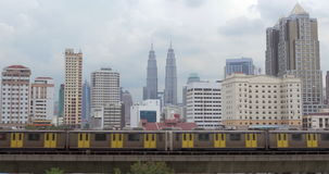 Panorama of Kuala Lumpur and moving trains, Malaysia. Kuala Lumpur cityscape with high-rise buildings and Petronas Twin Towers. Two overground metro trains stock footage