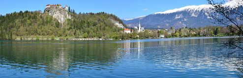 Crystal clear waters and snow-capped mountains at. Wide panorama of Lake Bled in the spring featuring Bled Castle and snowy mountain peaks reflecting in the Stock Photos