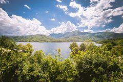 Panorama of a lake with green vegetation around. Natural basin with forest and mountains. royalty free stock photo