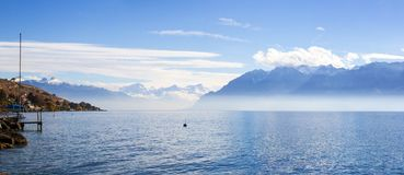 Panorama of Lake Leman or Lake of Geneva with morning mist over the water surface. At the background are the snow-covered Alps, at the right side is mountains royalty free stock photography