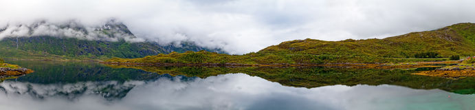 A panorama of a lake,  mountain and hill in foggy. A wide panorama photo mountain, waterfall and hill reflecting in a lake on a foggy day before rain Stock Images