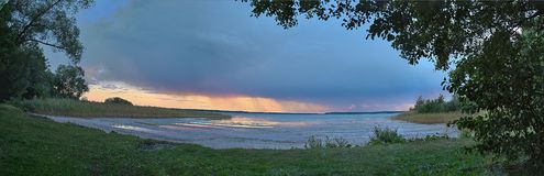 Panorama of a lake near Berlin in the evening with rainy clouds traversing in the background royalty free stock images