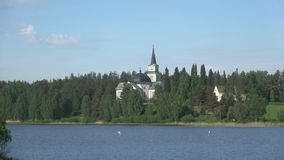 Panorama of lake Pappilanlahti overlooking the ancient Church of the city of Ruokolahti on a sunny june day. Finland stock footage