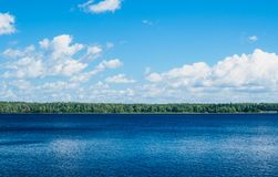 Panorama of the lake and with white clouds. Sunny summer day Stock Photography
