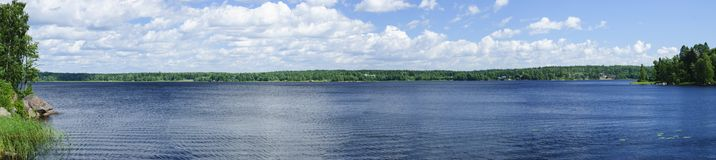 Panorama of the lake and with white clouds. Sunny summer day Royalty Free Stock Images