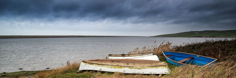 Panorama landscape of abandoned boats on shore of lagoon with dr Royalty Free Stock Image
