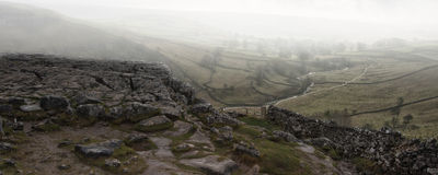 Panorama landscape foggy Autumnal view over limestone crag to va Stock Photos