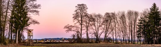 Panorama landscape with hunting tower after sunset in rural scenery against pink sky. Deer stand near Zettling Graz in Austria