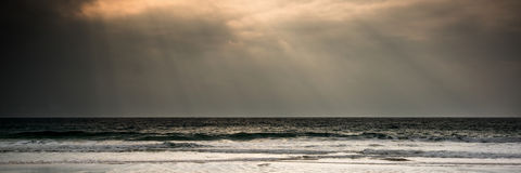 Panorama landscape image of sun beams over calm sea at sunset Royalty Free Stock Photography